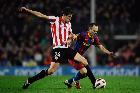 Martínez wins the ball over FC Barcelona midfielder Andres Iniesta